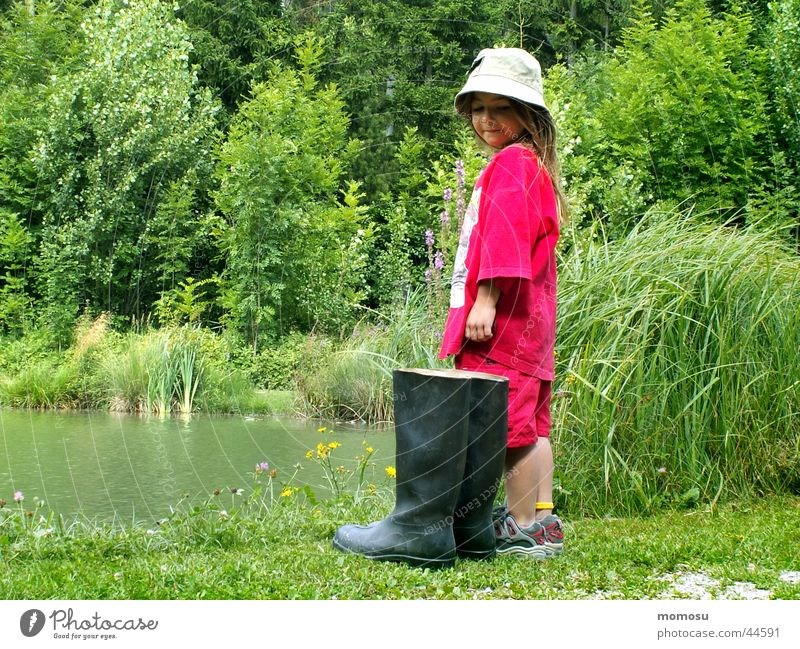 ... Should I or shouldn't I? Child Girl Rubber boots Large Small Habitat Meadow Grass Bushes Water