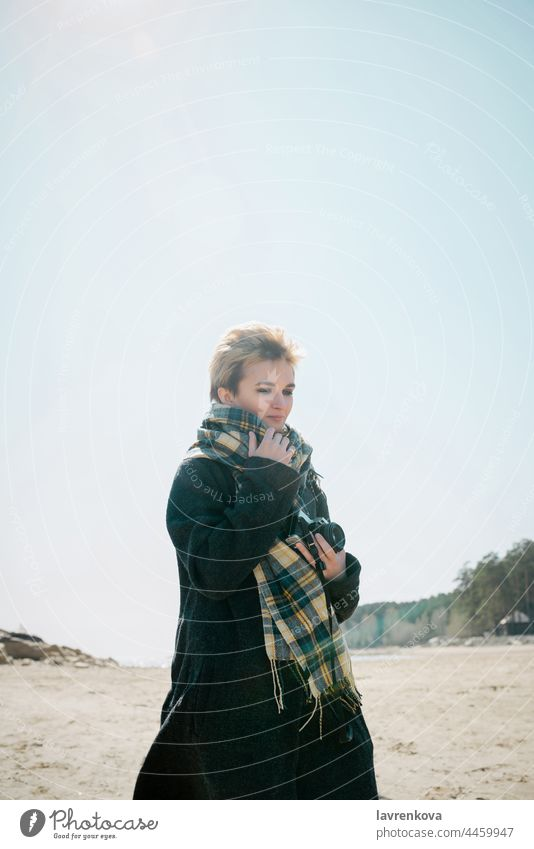 Young woman in a coat and scarft with camera standing on a beach in cold weather, adult autumn blonde caucasian fair weather female glasses happy landscape