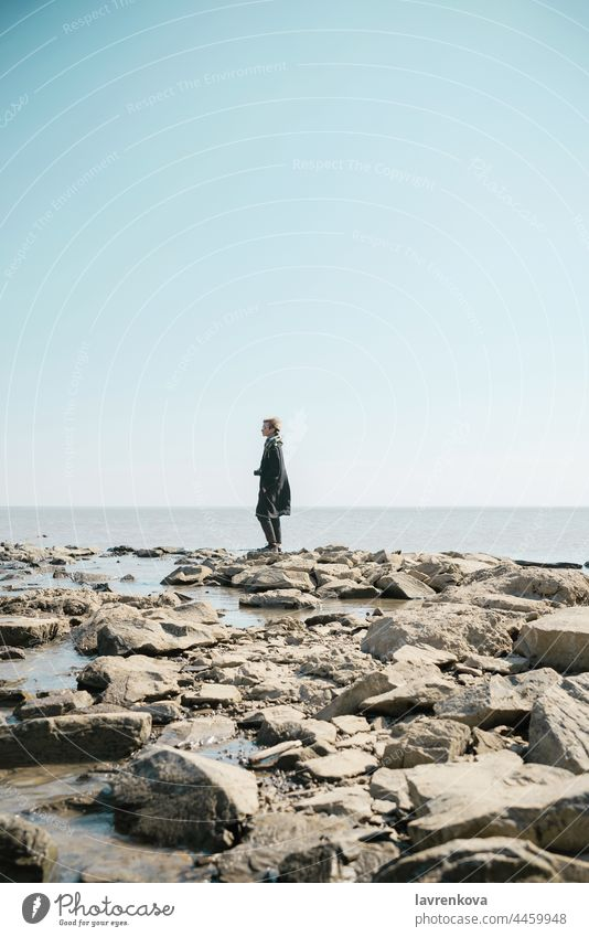 Young woman in a coat and scarft with camera standing on a deserted beach in cold weather adult autumn blonde caucasian fair weather female glasses happy