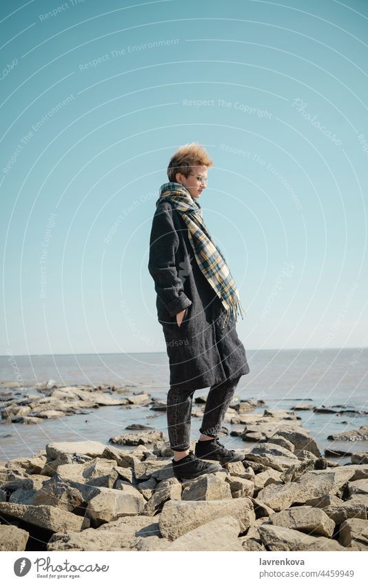 Young woman standing on a rocks on the beach in autumn female young blonde scarf coat cold fair weather seaside adult caucasian happy landscape lifestyle