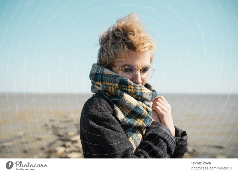 Young female in glasses warming herself on a beach alone coat autumn portrait young vacation face caucasian nature outdoors seaside sky travel water woman cold