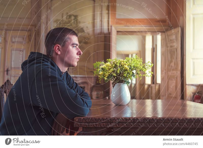 young man in profile sitting at a table with a vase full of yellow flowers portrait room inside interior door old ancient grungy elbows wood serious looking