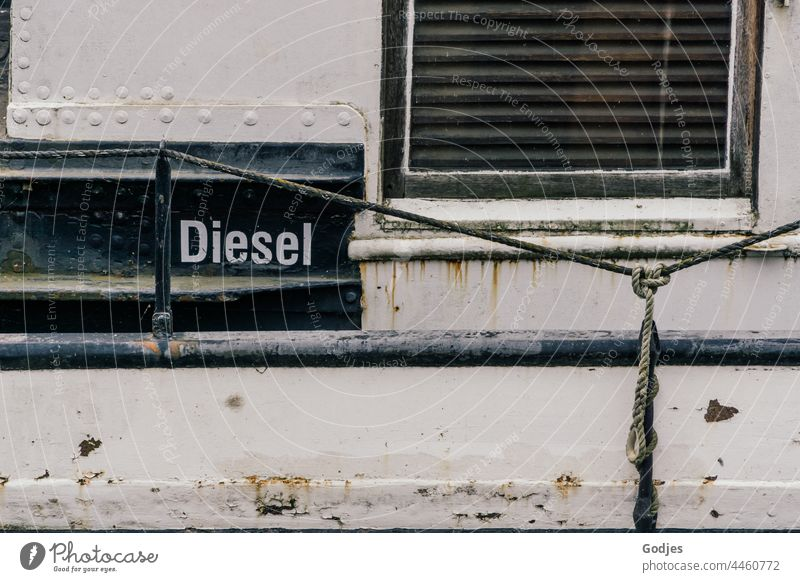 Steel wall of a ship with window and the inscription 'Diesel Steel construction Wall (building) Navigation Window Fuel Metal Exterior shot Steel carrier