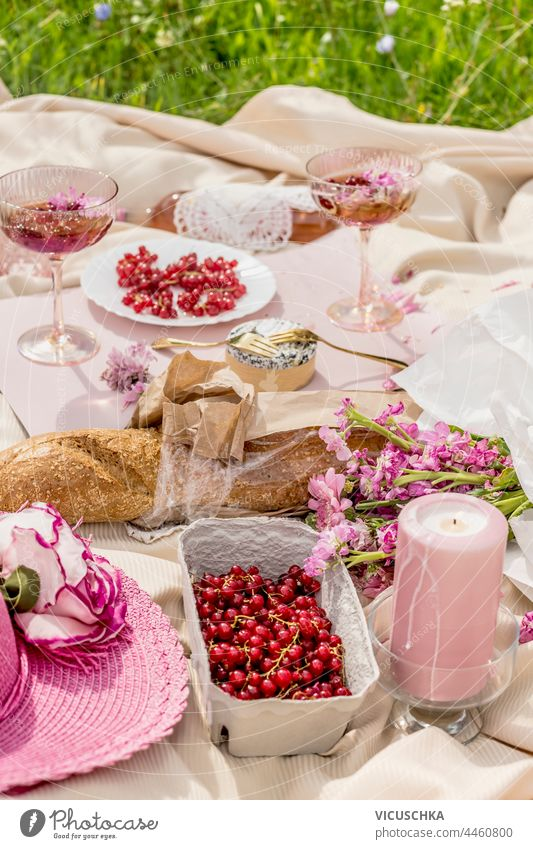 Aesthetic picnic with baguette, glasses of champagne, berries,  cheese , candles and pink flowers bunch on beige blanket. Outdoor aesthetic outdoor aesthetics