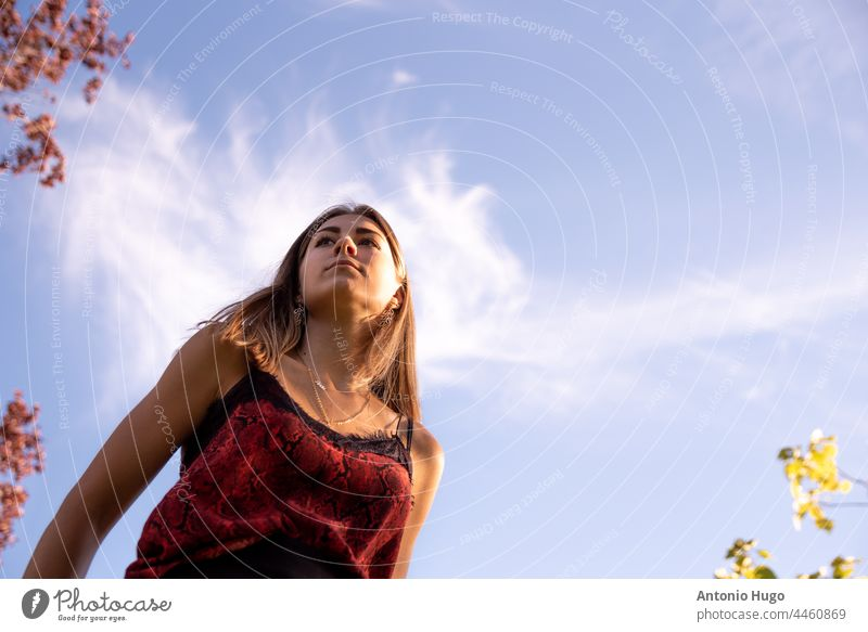 Portrait from below of a young blonde teenage girl. Blue sky background. portrait blue sky person female caucasian model look lady hair attractive fashion