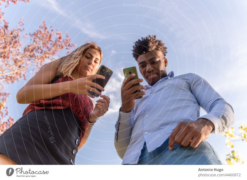 Young interracial couple using their mobile phones. View from below. Blue sky background. young view blue sky real people browsing message technology addiction