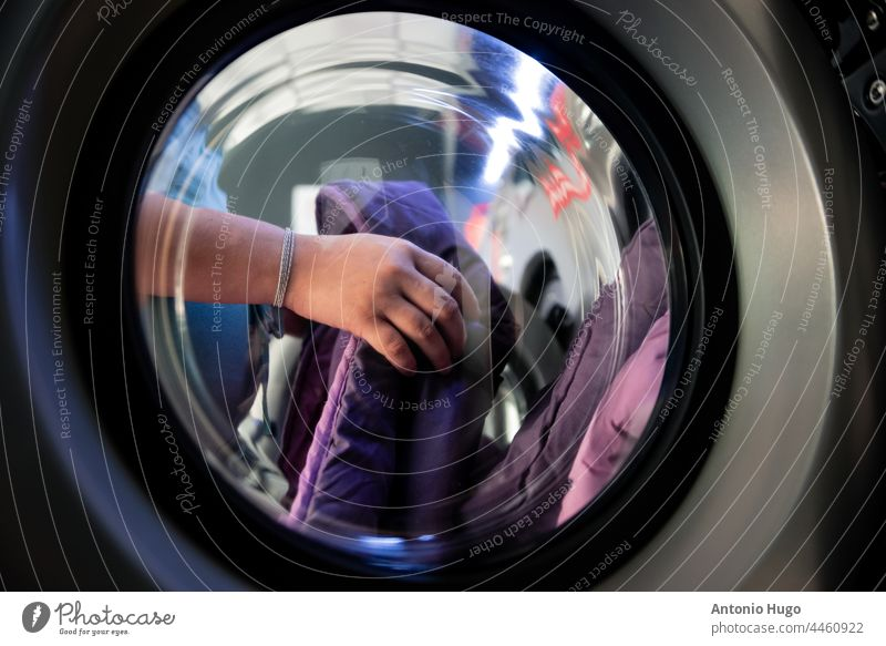 Woman hands in a laundry. Putting clothes into the washing machine. View from the glass of the washing machine. woman put artistic photo view laundromat