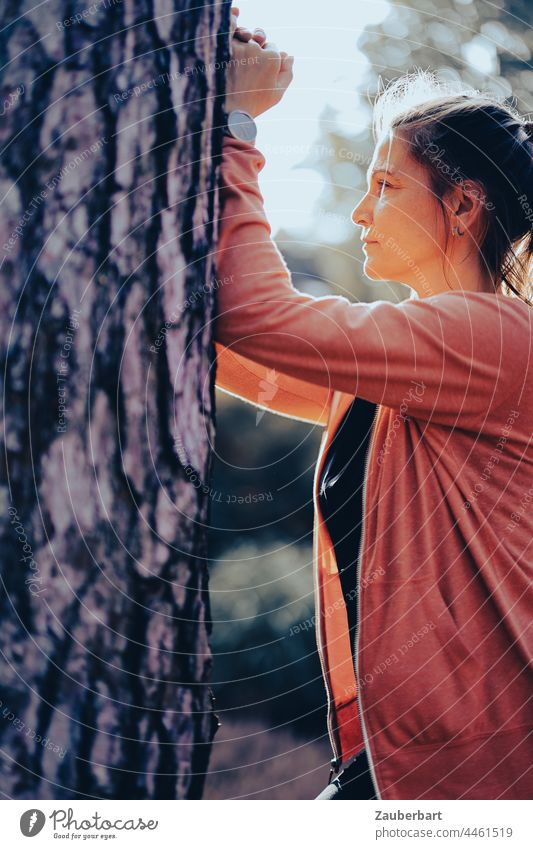 Sporty woman in orange jacket does stretching exercise on tree Woman Athletic Sports Orange Stretching Distend Warming up Lifestyle workout Body Tree Back-light