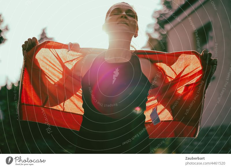 Sporty woman spreads arms after workout, backlit with red jacket Woman Athletic Back-light Red Arm Sun flares Silhouette Light Sunlight Body Walking Jogging