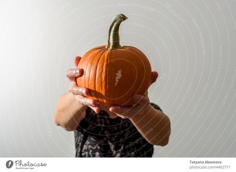 Woman holding pumpkin instead of head woman halloween female portrait jack-o-lantern hands harvest spooky creepy faceless anonymous anonymity