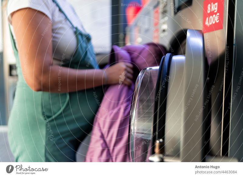 Pregnant woman in a laundry. Putting the clothes to be washed in the washing machine. pregnant basket laundromat laundrywoman crop into rear view dungarees