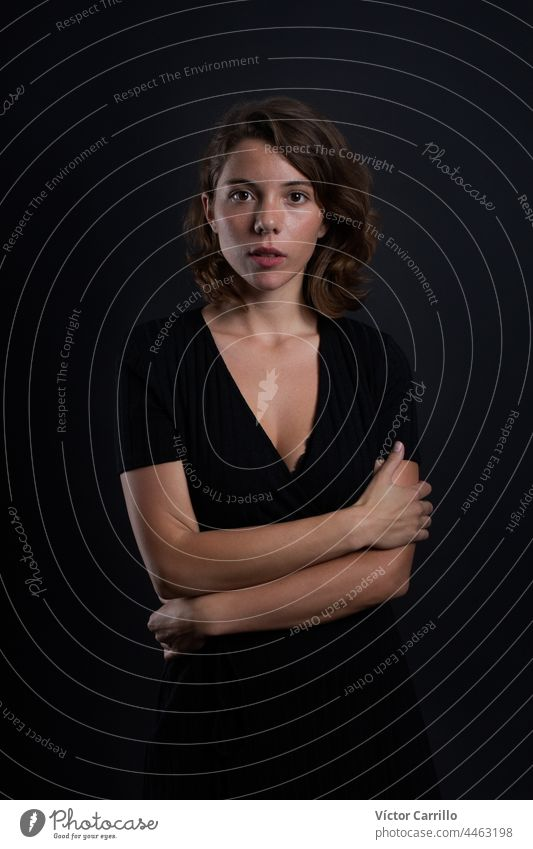 A young beautiful woman looking at the camera in a studio shot in black dress and background 20-25 adult attractive casual close-up concepts confident dark
