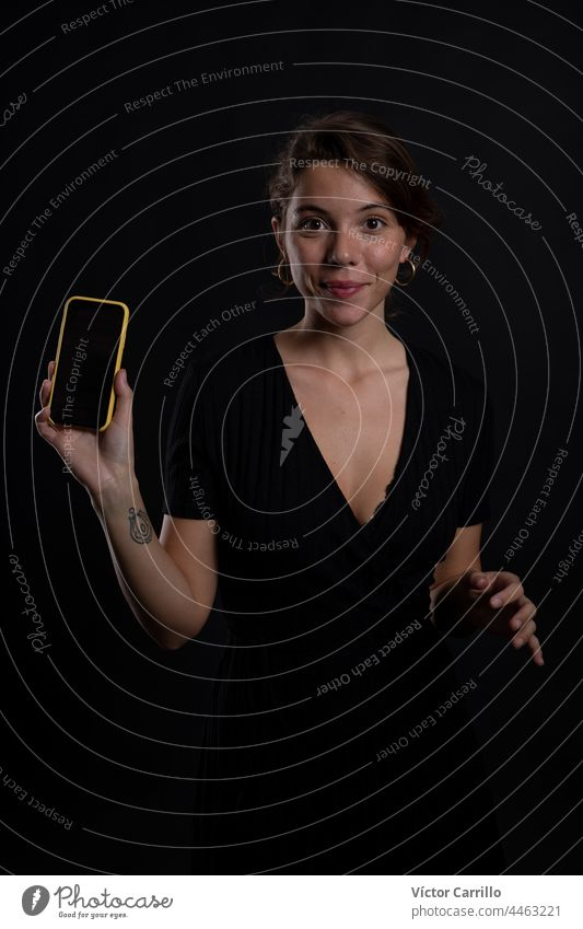 A young beautiful woman using a smartphone in a studio shot in black dress and background 20-25 adult attractive beauty brunette casual close-up concepts