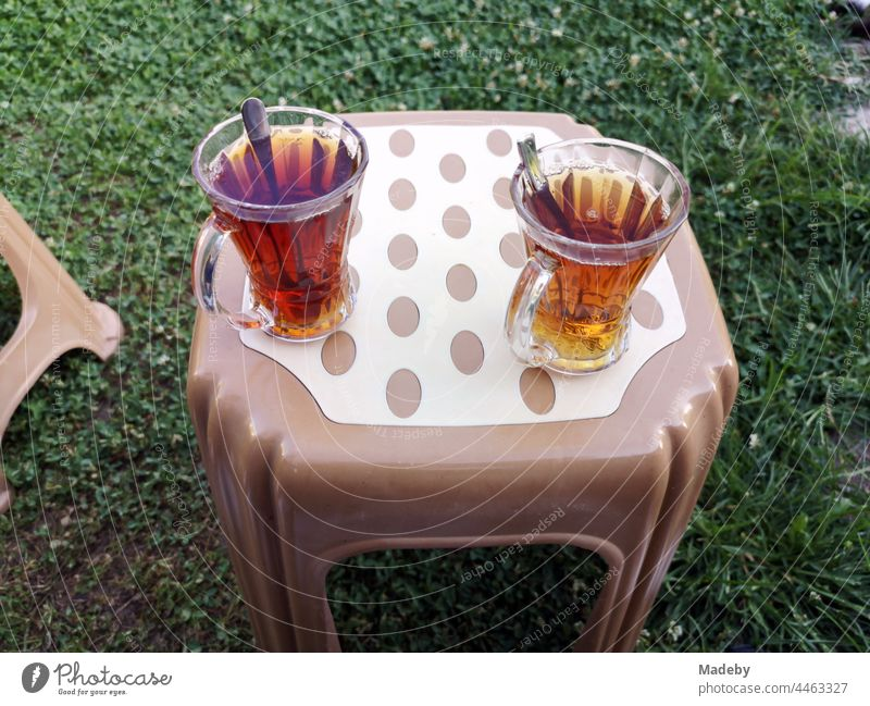 Turkish tea glasses with teaspoons and tea on a plastic stool in brown and beige on a green lawn in a garden in the village of Maksudiye in Sakarya province, Turkey