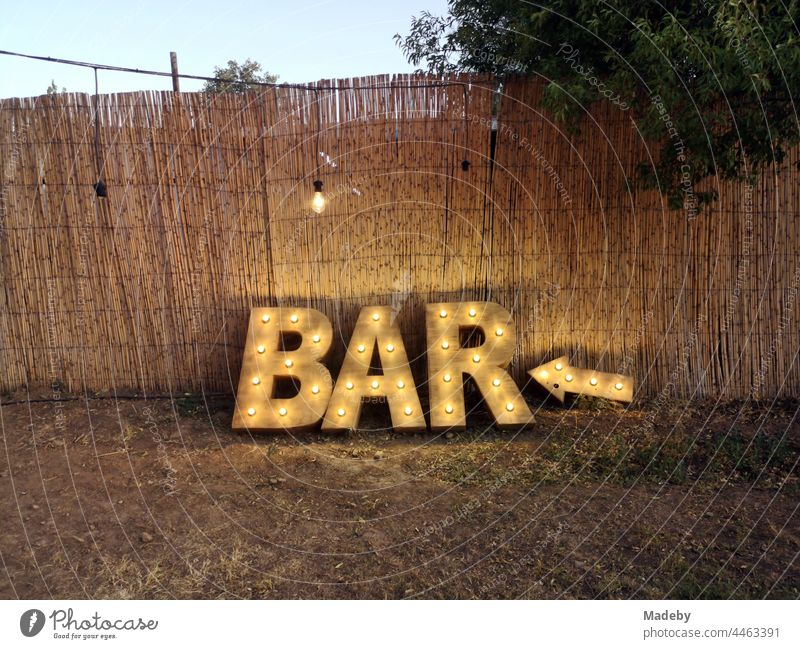 Illuminated indication of a bar in natural colors in front of color-matching brushwood fence in summer at dusk at a Turkish wedding in the park in Güzelbahce in Izmir province on the Aegean Sea in Turkey