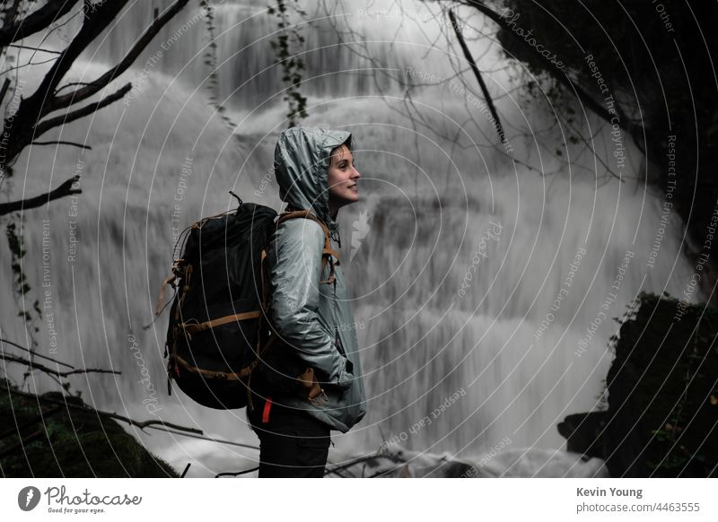 girl in front of a waterfall Waterfall Exterior shot Nature Colour photo River Wet Flow Rock Forest Backpack Natural