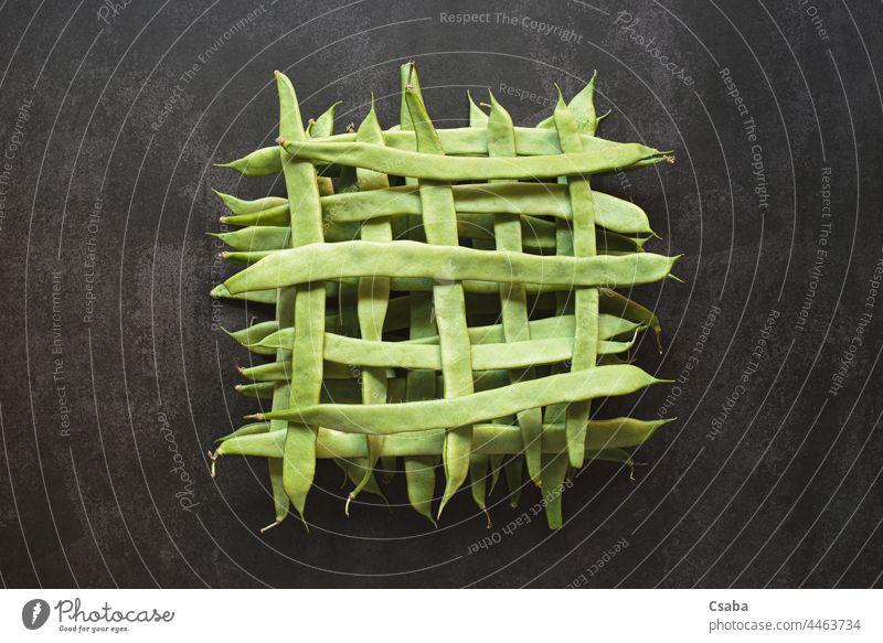 Top view of whole green beans in a geometric pattern on dark background shape vegetarian healthy food vegetable raw ingredient veggie top grid fresh ripe flat