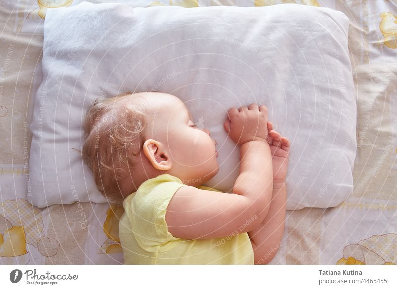 The baby sleeps on its side on a white pillow. beautiful sweet dream cute childhood bed face little toddler adorable young blanket asleep head kid bedtime