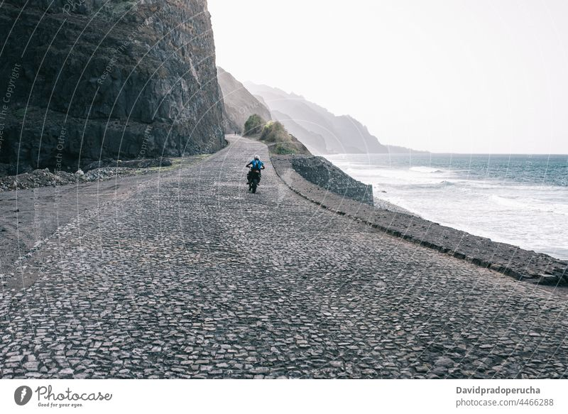 Faceless person riding motorbike on deserted road traveler motorcycle ride sea mountain trip santo antao cape verde cabo verde africa adult sit enjoy speed