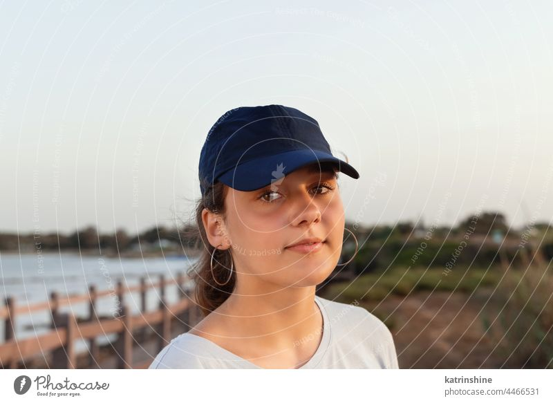 Teen girl in dark blue baseball cap standing by the sea at sunset. Cap mockup outdoor teenager adolescent Caucasian visor wearing t-shirts teen girl childhood