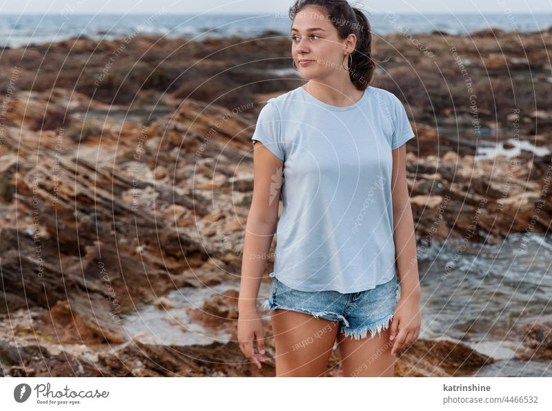 Teenage girl standing on cliff by the sea at sunset. shirt mockup teenager t-shirt blue Caucasian rock adolescent stone wearing childhood female happiness