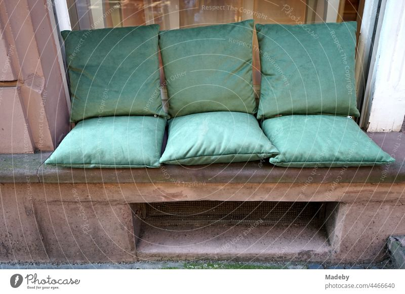 Elegant green seat cushions on red sandstone in the frame of a window in front of a hairdresser's in a beautiful old building in the North End of Frankfurt am Main in Hesse