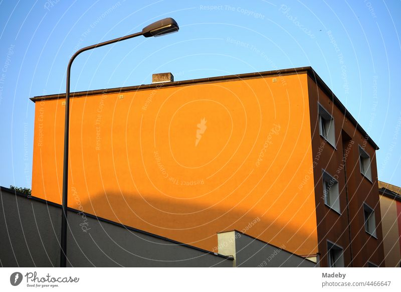 Orange painted facade without windows with street lamp in the light of the evening sun in the Bornheim district in Frankfurt am Main in Hesse