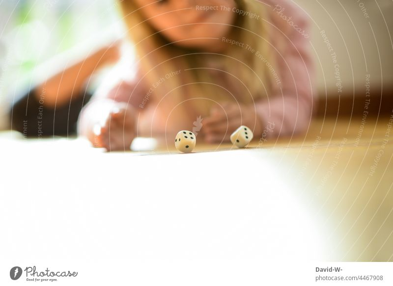 Child plays and rolls two dice Throw dice cubes Playing fun Girl Parlor games Joy Infancy Contentment