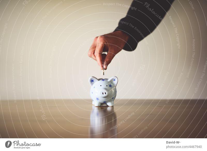burn a coin in a piggy bank Money box Save euro coins Hand Man Coin Euro Success Thrifty Future Forward-looking