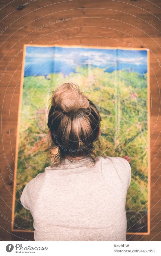 Woman in front of a map plans the holiday. Where is the trip going? Map vacation planning travel Adventure Anticipation Preparation Planning splayed Euphoria