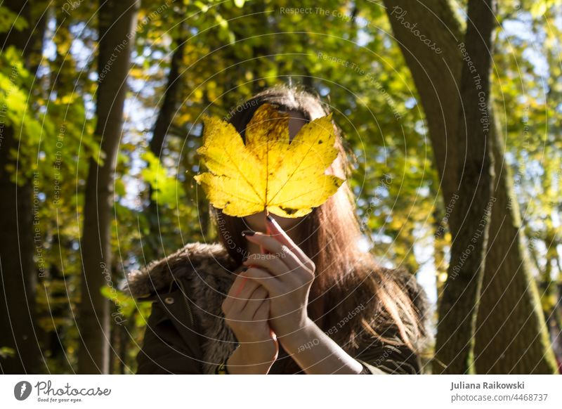 Woman with autumn leaf in front of face in forest Autumn Nature Autumn leaves Exterior shot Young woman Early fall Autumnal Autumnal colours Automn wood