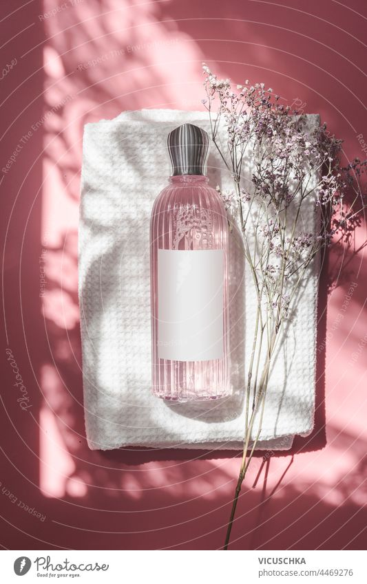 Pink cosmetic bottle with blank label on white towel on pink background in sunlight with ornament shadow. Top view top view toner pastel transparent wellness