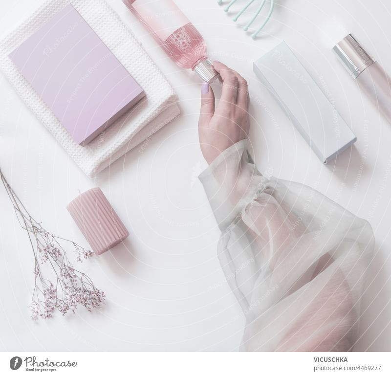 Women hand holding pink  cosmetic bottle on modern beauty  background with packaging boxes, candles and flowers. Top view. Pastel muted color women top view