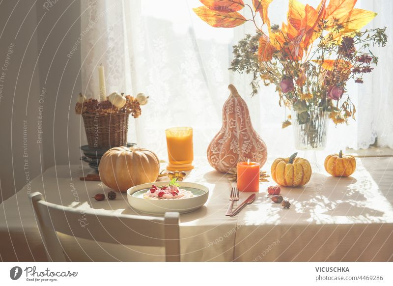Autumn breakfast table with pumpkins, bunch of orange fall leaves and flowers, waffles with whipped cream and candles. Domestic still life at window with sunlight