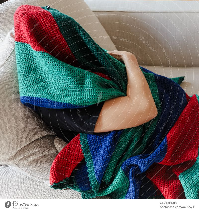 Man hiding under a colorful wool blanket on the sofa Human being arm Wool blanket variegated Sofa wrapped Green Red Blue stop Hide crease Textiles Cloth