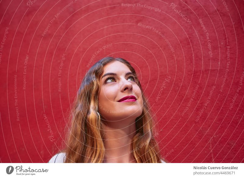 Headshot of blonde woman looking up standing in front of an intense red wall. person portrait fashion caucasian young model trendy stylish glamour hipster