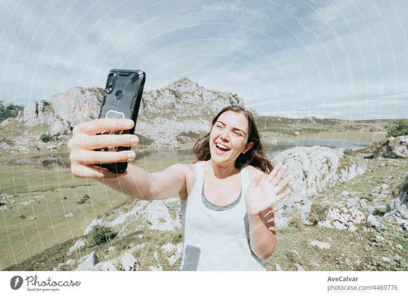 Cheerful nice woman smiling and making selfie while resting on the mountain hills, bright day at the lakes on the top of the mountains, peace sign photo person