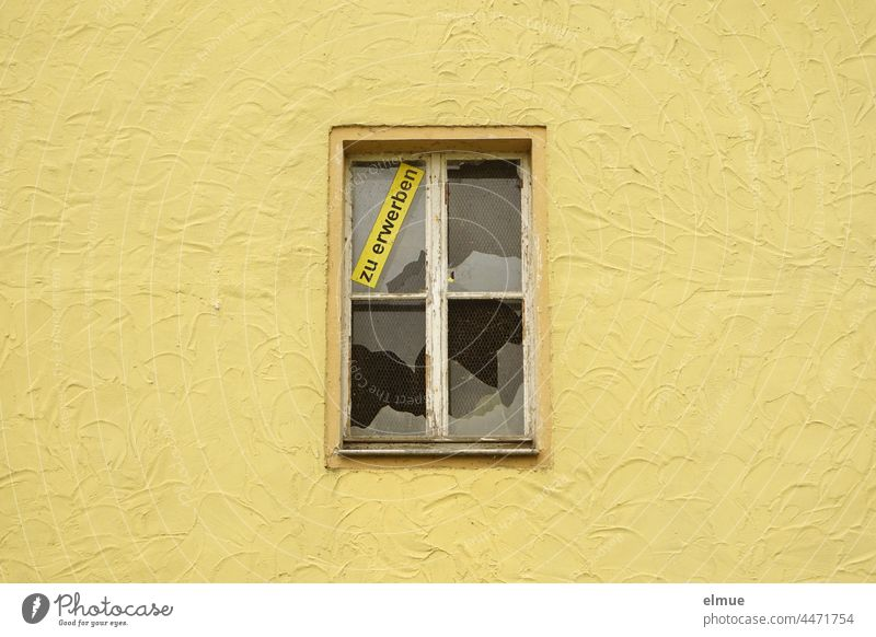 a yellow wall of a house with a broken window and the sign - to acquire -. real estate obtainable House (Residential Structure) Real estate market Pane Window