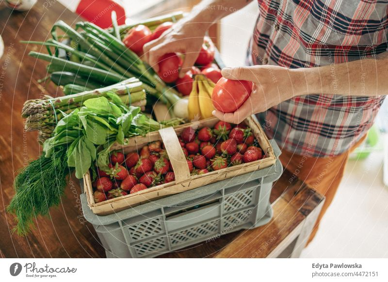 Man unpacking his groceries in the kitchen at home hand people person unpacking groceries agriculture asparagus basket box buying cooking crate delicious