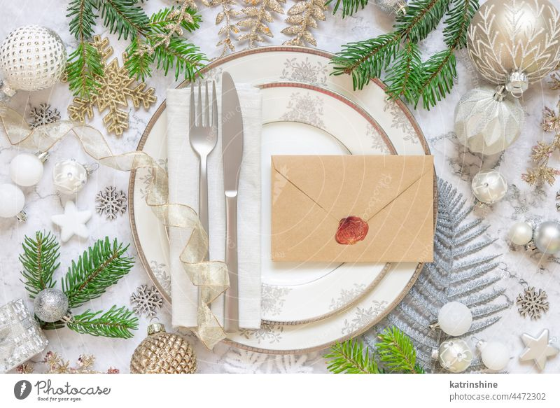 Festive table setting of with fir tree branches and Christmas decorations. Envelope mockup christmas ornaments holiday new year white marble silver golden