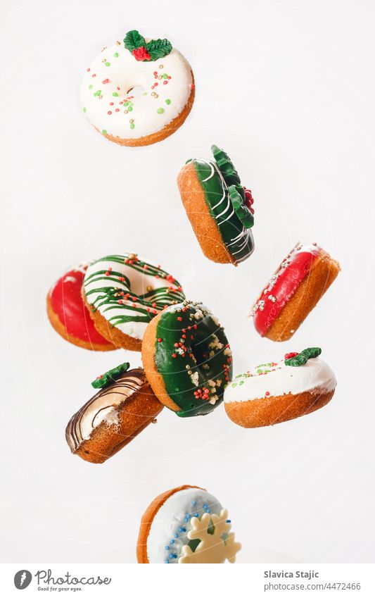 Flying Christmas donuts. Colorful doughnuts with sprinkles falling or flying in motion against white background 3d american bakery bread breakfast cake