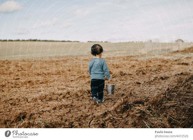 Rear view child walking with bucket through fields Child childhood Caucasian one one person Autumn Authentic Cute Lifestyle Joy Happy caucasian kid Infancy