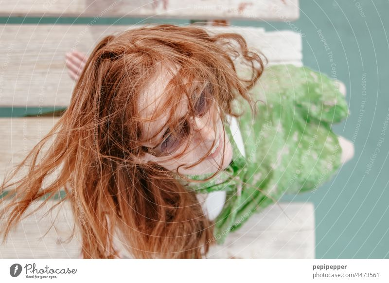 redhead woman in sunglasses sitting on a jetty photographed from above red-haired woman red hair Red-haired Redheads Woman Face of a woman women portrait pretty