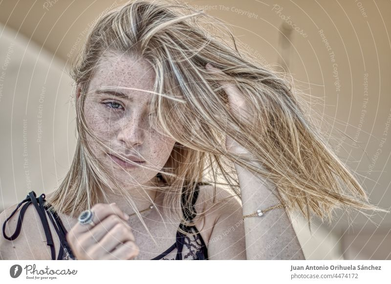 Young blonde woman with freckled face and hair blowing in the wind pretty green eyes lifestyle people attractive young woman girl adult person white blond hair