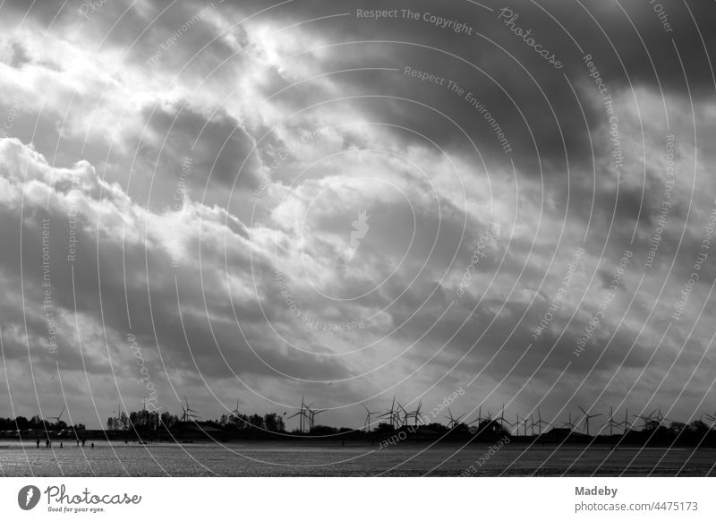 Wind turbines behind the dike at the coast of the North Sea in Bensersiel at the Wadden Sea with wind and clouds in East Frisia in Lower Saxony, photographed in neo-realistic black and white
