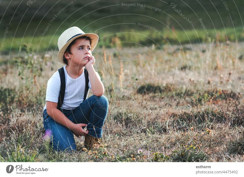 Thoughtful child with white t-shirt and hat childhood nostalgic thoughtful kid loneliness lonely future expression freedom innocence unhappy portrait serious