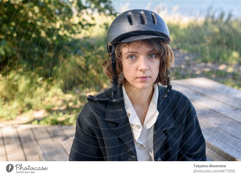 Young woman in helmet bicycle female cycling biking lifestyle ride leisure active activity city park curly summer outdoor adult bike one person riding enjoyment