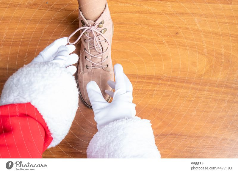 Santa Claus is helping a girl tie her shoelaces assistance bonding casual child childhood claus close up day encouragement family fatherhood foot footwear
