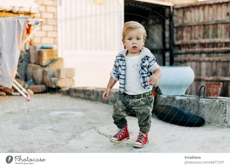 A charming little boy is walking in the backyard of a farm barn background little farmer kid baby building outdoors cute white young child family summer nature