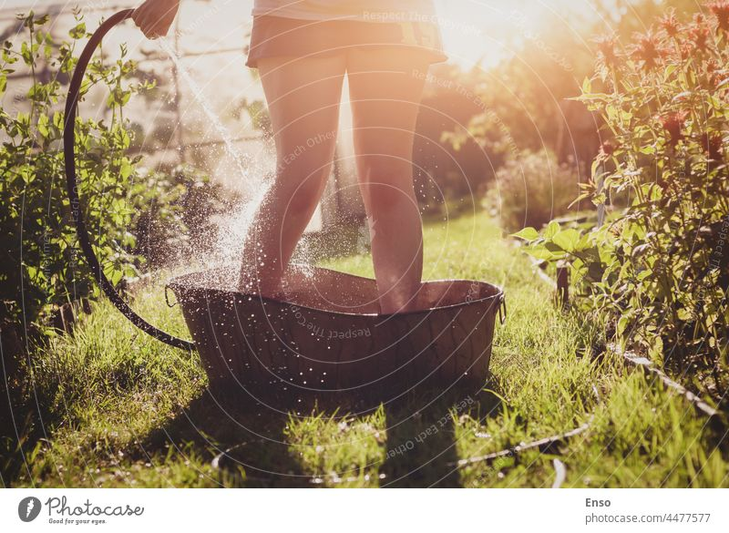 Bathing in the summer garden, woman pouring water on her feet from garden hose standing in an iron bath on garden path in sunlight showering bathing legs